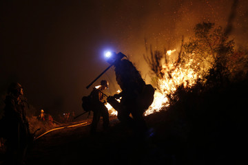 A firefighter uses a drip torch while controlling the Springs Fire near Newbury Park, California
