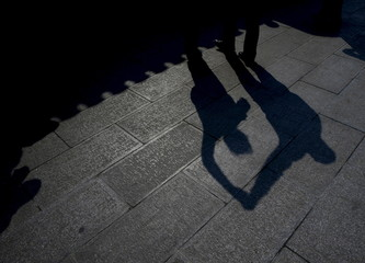 A man and a woman cast their silhouettes as they perform square dancing at a park square in Beijing