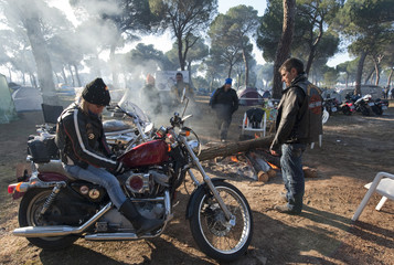 "Motorcyclists gather around a fire during the ""International Winter Motorcycle Rally. Pinguinos (Penguins)"" in Puenteduero, near Valladolid"