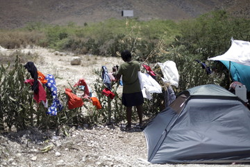 A woman picks up dry laundry at a camp for returned Haitians and Haitian-Dominicans, near the border between the Dominican Republic and Haiti, in Malpasse