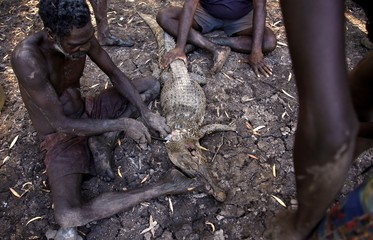 Australian Aboriginal hunter Roy Gaykamangu of the Yolngu people sits by a billabong and cuts up a crocodile he just shot dead near the 'out station' of Yathalamarra, located on the outksirts of the community of Ramingining in East Arnhem Land