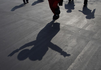 A shadow of Mickey Mouse is cast as the Disney character waves to visitors at Tokyo Disneyland in Urayasu