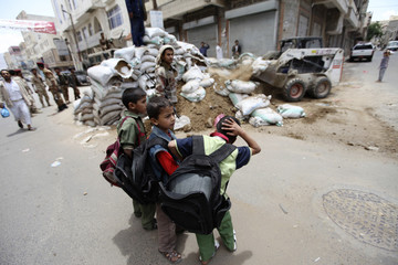 Boys look on as the dismantling of barricades in Sanaa