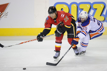 Edmonton Oilers' Belanger tries to get the puck from Calgary Flames' Iginla during their NHL hockey game in Calgary.