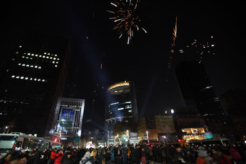 Revellers watch as fireworks go off as they welcome the new year near the Bosingak pavilion in central Seoul