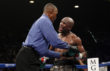 Floyd Mayweather Jr. complains that Marcos Maidana bit him as referee Kenny Bayless examines his glove during their title fight at the MGM Grand Garden Arena  in Las Vegas