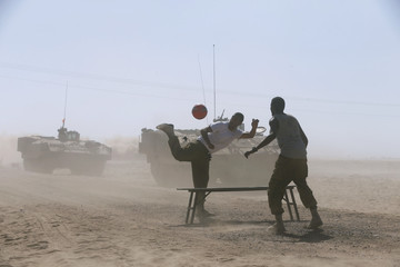 Israeli soldiers play with a ball near the Israeli border with the Gaza Strip