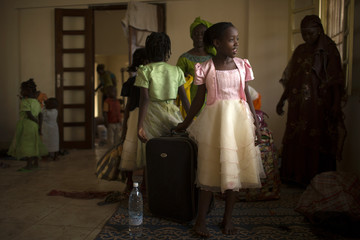 A girl smiles as Muslim families, fleeing ongoing sectarian violence, prepare to be evacuated by air from consulate of Mauritania in Bangui