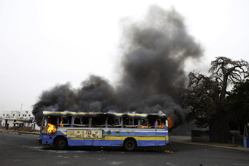 A public bus set on fire by anti-government protestors burns during street clashes with police in Senegal's capital Dakar