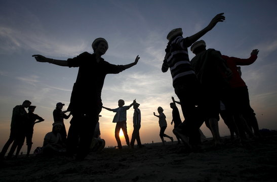 Men are silhouetted as they dance to celebrate during sunset at a beach in Karachi