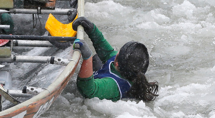 A member of Team Chez Victor falls in the water while competing during the Ice Canoe race at the Quebec Winter Carnival in Quebec City