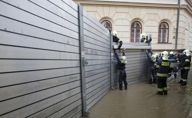 Firefighters assemble a water barrier in the medieval Kampa district to prevent water spilling into streets in Prague