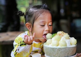 Kid girl eating melon Bing Su Korean Dessert.
