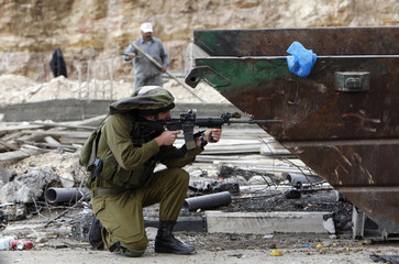 An Israeli soldier take position during clashes at Qalandiya checkpoint