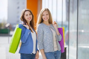Two stylish girls with shopping bags