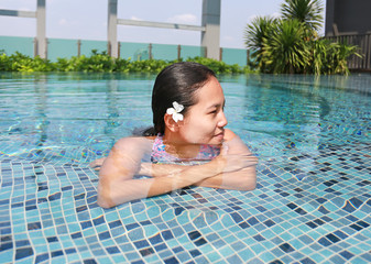 Young asian woman relax in swimming pool.