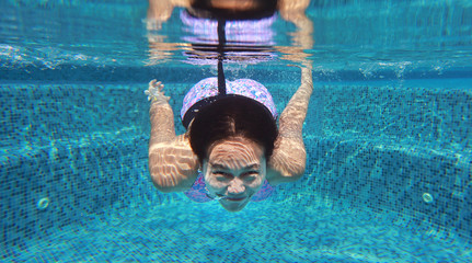 Young asian woman having fun underwater in swimming pool.