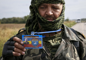 A pro-Russian separatist shows his identification card with his battalion and name to Ukrainian journalists at a checkpoint near the town of Slavyanoserbsk