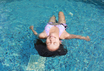 Young woman floating on the water surface of the swimming pool.