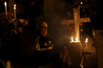 A boy sits next to a grave of a relative on the Day of the Dead, at a cemetery of Metepec on the outskirts of Mexico City