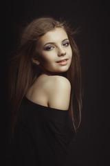 Smiling young model in black dress posing at studio