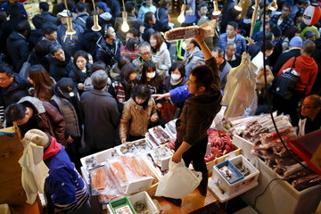 Fishmongers offer their goods for sale as people crowd Ameyoko market to shop for food and goods ahead of the New Year holidays in Tokyo