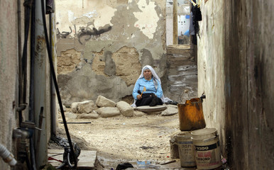 A Palestinian refugee sits outside her house in the Gaza Strip