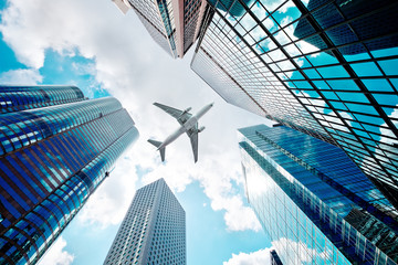 Airplane flying over business skyscrapers