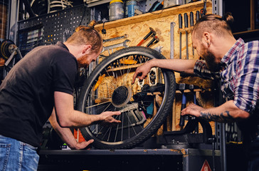 Two bearded mechanics fixing town bicycle in a workshop.