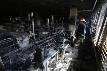 A firefighter inspects the Standard Group garment factory which was on fire in Gazipur