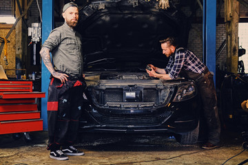 Two mechanics fixing car's engine in a garage.
