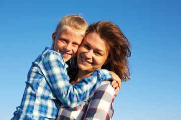 Beautiful mum with cute little child on her back. Parent and child smile, enjoy life and looking to camera. Closeup.