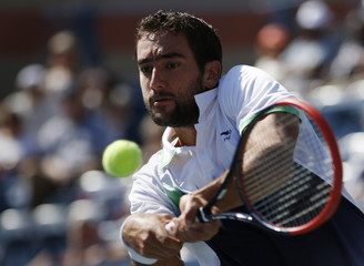 Marin Cilic of Croatia hits a return to Tomas Berdych of the Czech Republic during their quarter--final match at the 2014 U.S. Open tennis tournament in New York