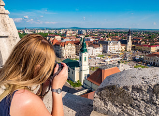 Woman tourist taking pictures of Oradea city main square. Focus on tourist hands