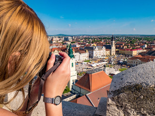 Tourist taking pictures from the City Hall Tower in Oradea, Romania. Focus on tourist