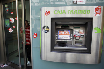 "A sticker that reads ""Closed for general strike"" covers the screen of an ATM machine as a man walks out of a bank during a nationwide general strike in central Madrid"
