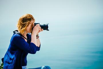 Female traveler taking a photo on the seaside