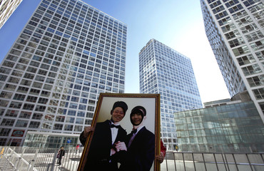 Women pose for photographs with a picture board displaying a wedding portrait of gay grooms during a homosexuality promotion campaign on Valentine's Day at a business district in central Beijing