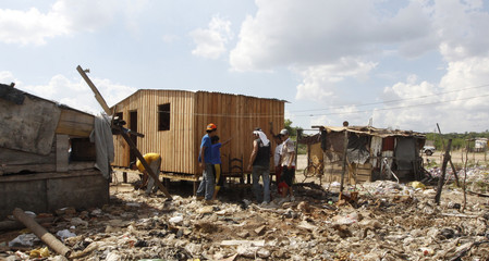 "Members of ""A Roof for Paraguay"", a non-governmental organisation (NGO), build a home for poor Paraguayans near Asuncion"
