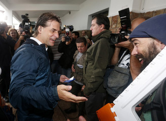 Presidential candidate Luis Lacalle Pou of the National Party jokes with a photographer after casting his vote at a polling station in Canelones