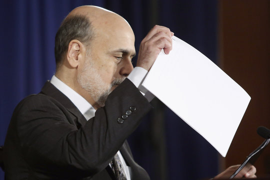 U.S. Federal Reserve Chairman Bernanke readies his notes as he begins his final planned news conference before his retirement, at the Federal Reserve Bank headquarters in Washington