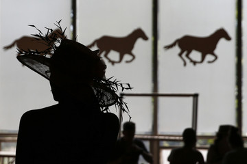 A woman is seen in silhouette at Belmont Park before the 2014 Belmont Stakes in Elmont, New York