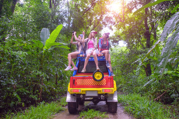 woman enjoy traveling adventure by sitting on rack roof of the convertible off road car and looking at the top of rainforest