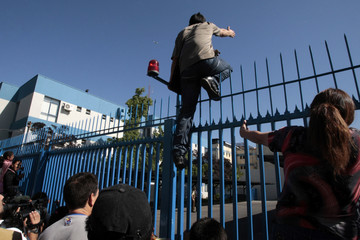A relative of an inmate climbs a fence as they gather outside San Miguel public prison, after a fire broke out in the building, killing 81 inmates, in Santiago