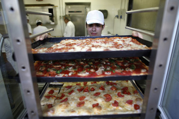 "Gibranth holds a baking tray with pizza in the kitchen of the ""Master Pizzaioli"" school where he studies to be a pizza chef in Rome"