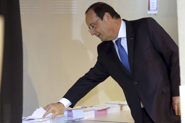 France's President Francois Hollande selects ballots before enter the polling booth in the European Parliament election in Tulle