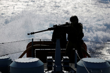 An Israeli soldier fires a machine gun as he takes part in a drill simulating the targeting of an infiltrated enemy vessel and the evacuation of a patrol boat, in the Mediterranean Sea off the coast of Ashdod