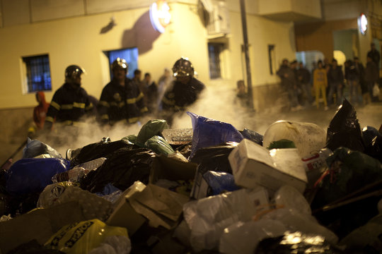 Firefighters extinguish burning rubbish bags, which were set on fire by residents frustrated by piling rubbish due to a strike by garbage collectors in Jerez de la Frontera