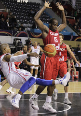 Dominican Republic's Flores falls after colliding with Canada's Anthony during their first round Basketball match of the FIBA Americas Championship