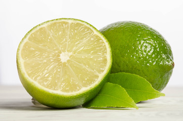 Juicy lime with its leaves on wooden background